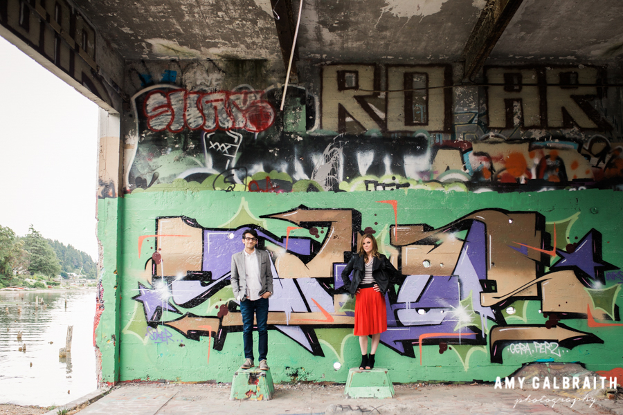 engaged couple standing in front of graffiti backdrop