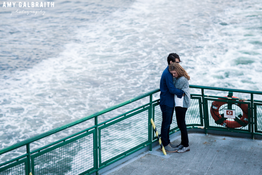 couple standing on the back of washington ferry boat to seattle