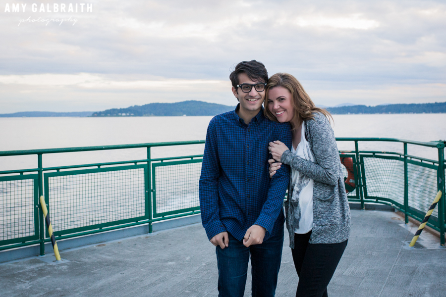 couple laughing as their ride a ferry during their engagement session