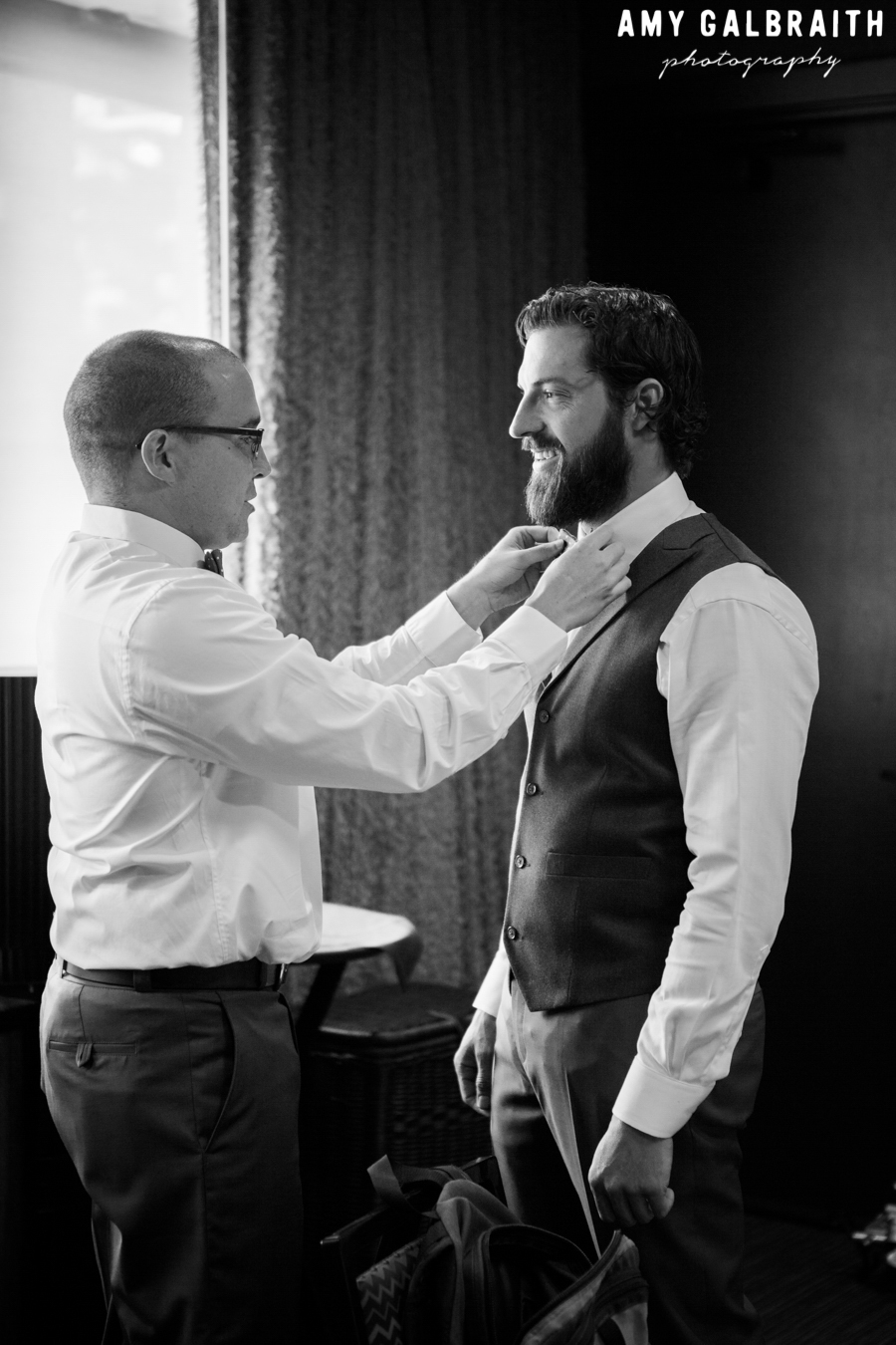 groomsman adjusting bow tie for groom