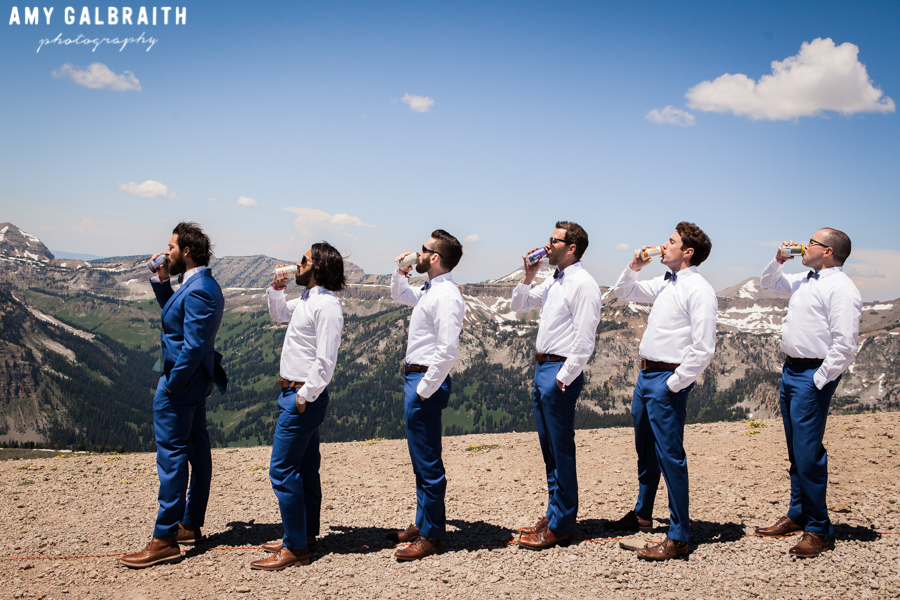 groomsmen and groom drinking beers on jackson hole mountain top