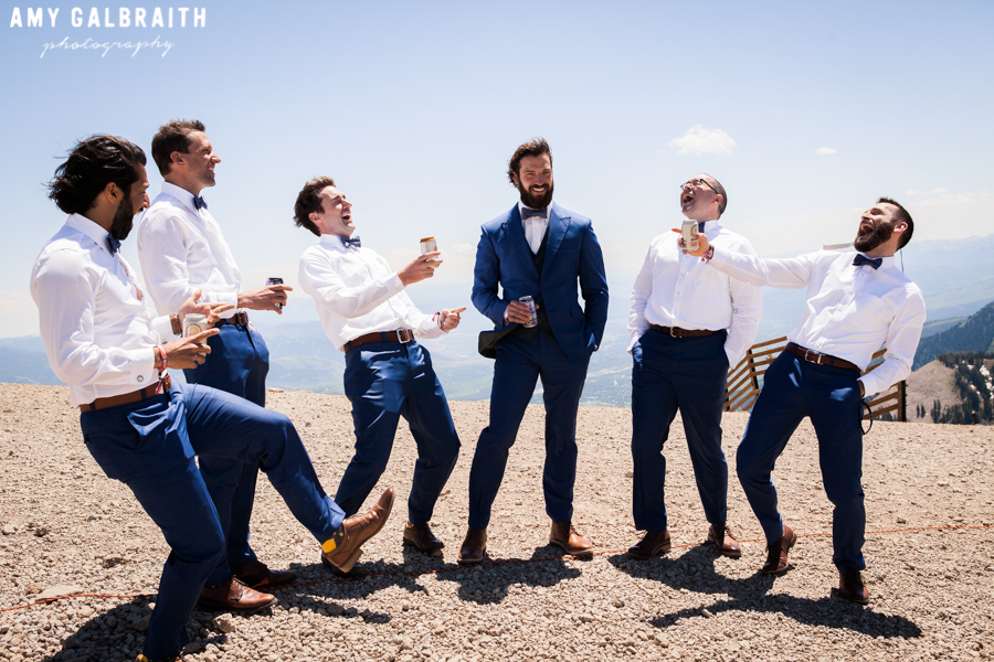 groomsmen laughing together on mountain top
