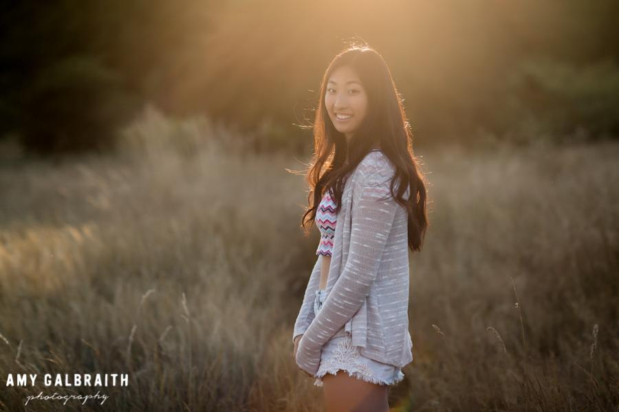 high school senior in grey sweater at sunset