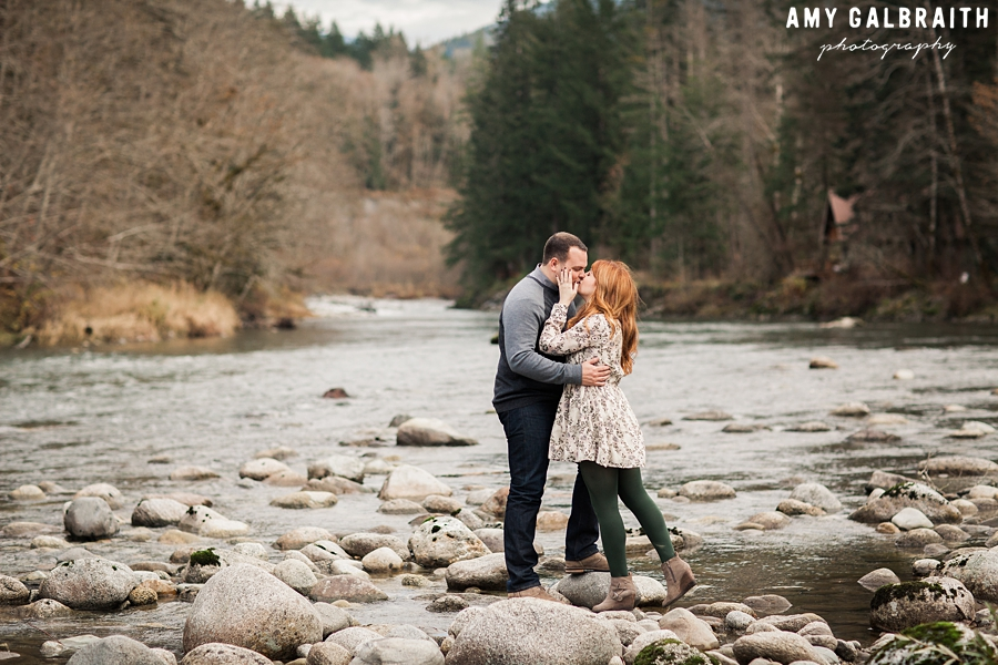 a couple kisses next to the river in skykomish washington