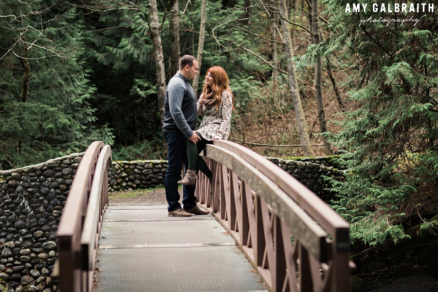 a couple chatting together on a bridge in the woods at stevens pass