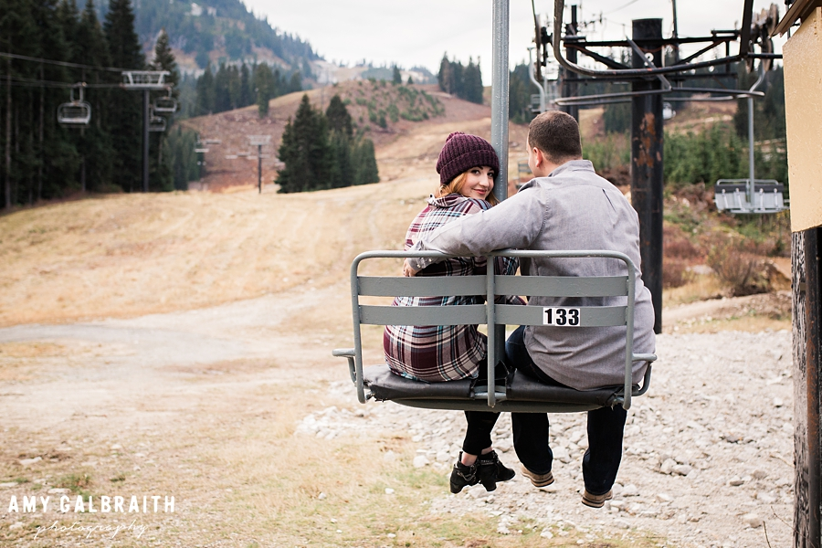 a couple sitting on the brooks chairlift during their engagement session at stevens pass washington