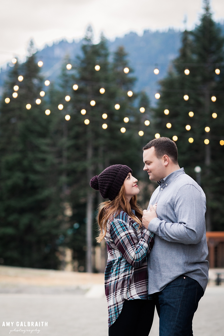 a couple having an intimate moment under the bistro lights during their stevens pass engagement session