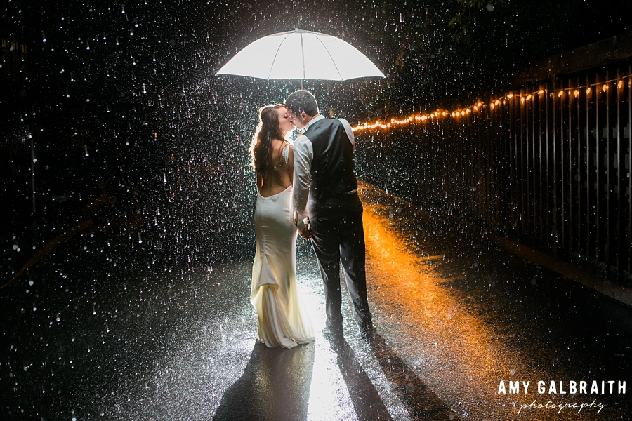 bride and groom in the rain at night at the manor house at pleasant beach