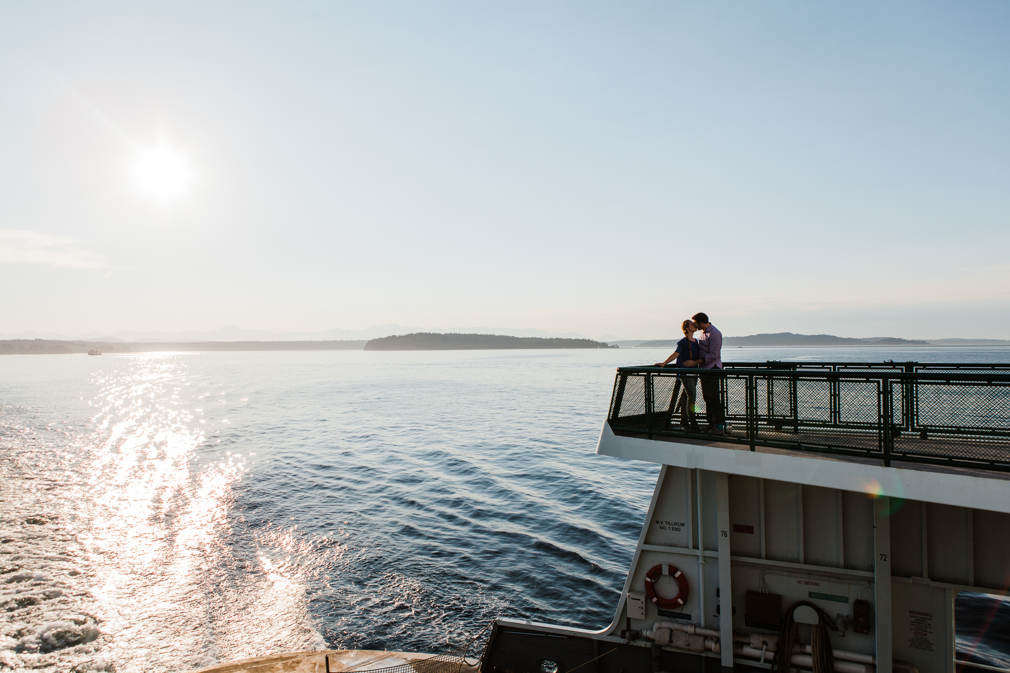 couple riding on a ferry at sunset