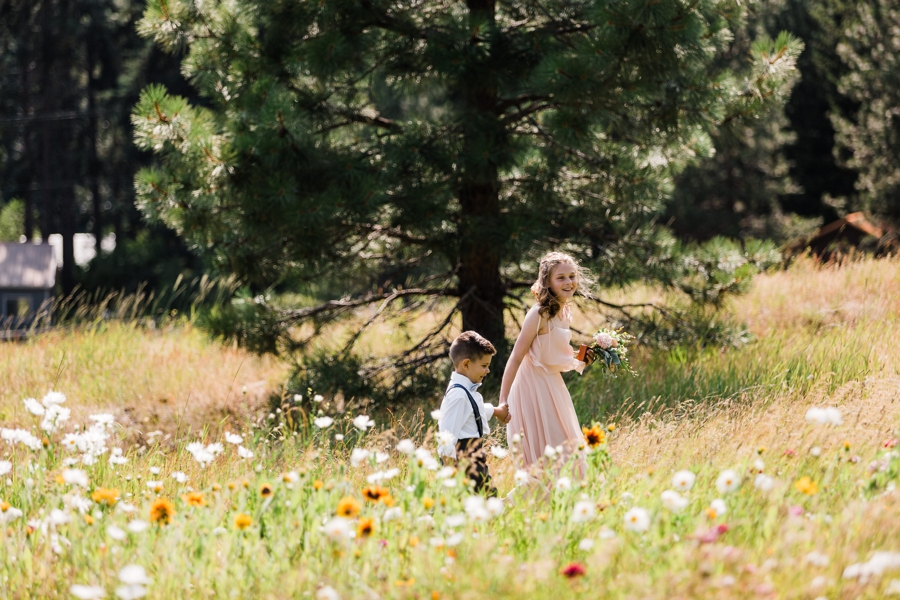 adorable ring bearer and flower girl walk through the wildflowers at Brown Family Homestead